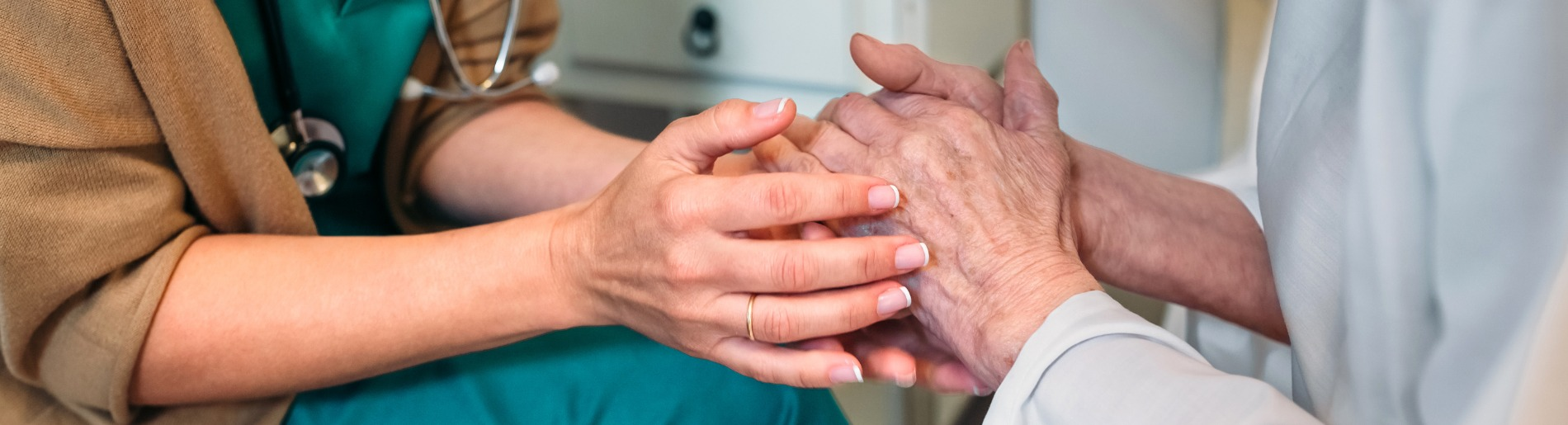 Nurse holding elderly persons hands